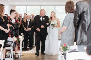 Bride gets walked down the aisle at her wedding